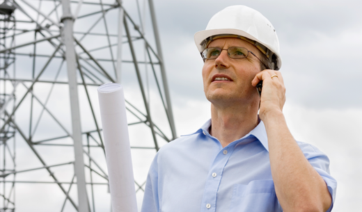 IMage of a man in hardhat on phone in front of tower