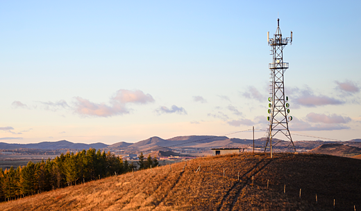 Image of tower in brown wheat field with mountains behind